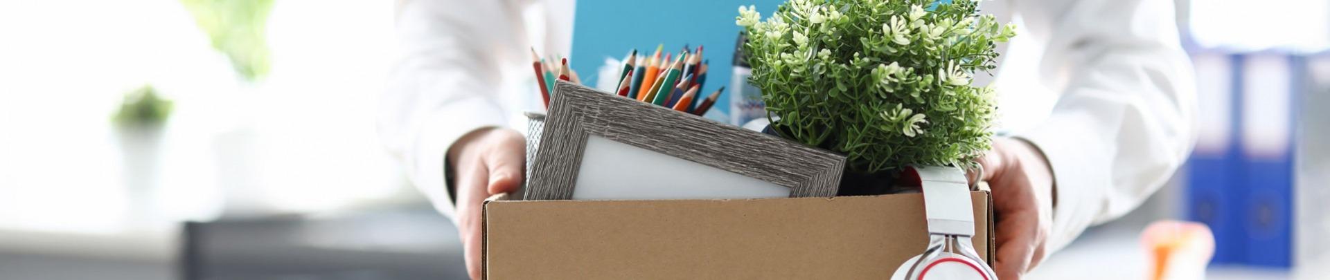 man vertrekt van kantoor met doos met persoonlijke spullen